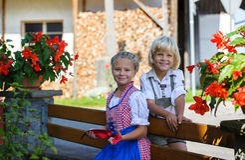 Ragazzo bavarese felice con la sorella sull'azienda agricola in Germania Fotografia Stock