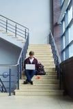 Ragazzo bello che si concentra sul lavoro in computer portatile che si siede sulle scale Fotografia Stock