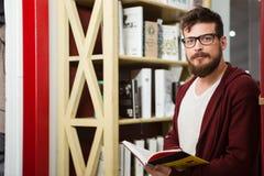 Ragazzo bello con la barba in libro di lettura di vetro Fotografia Stock