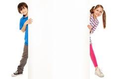 Due bambini che mostrano nuova pubblicità in bianco Immagini Stock Libere da Diritti