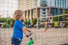 Ragazzo biondo attivo del bambino che conduce bicicletta nel parco vicino al mare Bambino del bambino che sogna e che si diverte  Fotografie Stock Libere da Diritti