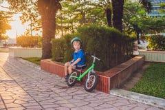 Ragazzo biondo attivo del bambino che conduce bicicletta nel parco vicino al mare Bambino del bambino che sogna e che si diverte  Fotografia Stock