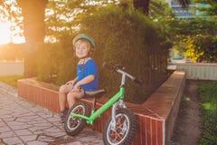 Ragazzo biondo attivo del bambino che conduce bicicletta nel parco vicino al mare Bambino del bambino che sogna e che si diverte  Immagine Stock
