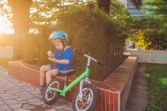 Ragazzo biondo attivo del bambino che conduce bicicletta nel parco vicino al mare Bambino del bambino che sogna e che si diverte  Fotografie Stock