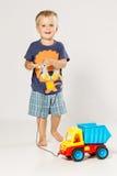 Ragazzo biondo che gioca con la piccola automobile di plastica fotografia stock libera da diritti