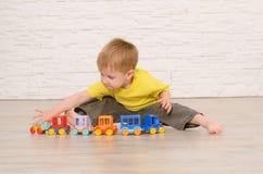 Ragazzo biondo che si siede sul pavimento e sui giochi nel children& x27; treno di s fotografie stock