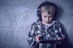 Ragazzo biondo del bambino che ascolta la musica o il film di sorveglianza con le cuffie e che usando tavola digitale Immagine Stock