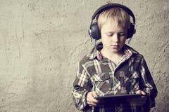 Ragazzo biondo del bambino che ascolta la musica o il film di sorveglianza con le cuffie e che usando tavola digitale Immagine Stock Libera da Diritti