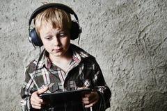 Ragazzo biondo del bambino che ascolta la musica o il film di sorveglianza con le cuffie e che usando tavola digitale Fotografie Stock Libere da Diritti