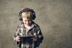 Ragazzo biondo del bambino che ascolta la musica o il film di sorveglianza con le cuffie e che usando tavola digitale Fotografia Stock
