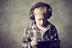 Ragazzo biondo del bambino che ascolta la musica o il film di sorveglianza con le cuffie e che usando tavola digitale Immagini Stock