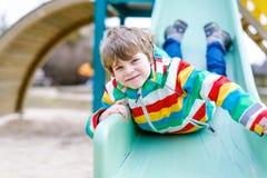 Ragazzo biondo felice del bambino divertendosi e facendo scorrere sul campo da giuoco all'aperto Immagine Stock Libera da Diritti