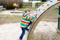 Ragazzo biondo felice del bambino divertendosi e scalando sul campo da giuoco all'aperto Fotografia Stock