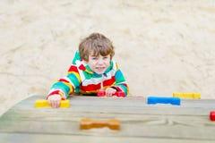 Ragazzo biondo felice del bambino divertendosi e scalando sul campo da giuoco all'aperto Immagine Stock