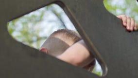 Ragazzo biondo felice del bambino divertendosi e scalando sul campo da giuoco all'aperto Svago di estate, della primavera e di au video d archivio