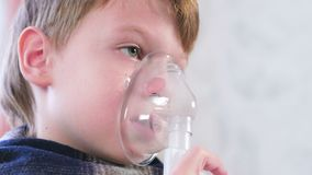 Ragazzo biondo malato che inala attraverso la maschera dell'inalatore, vista del fronte del primo piano Utilizzi il nebulizzatore archivi video