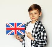 Ragazzo biondo sveglio che posa con la bandiera di britannici Immagine Stock