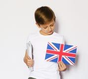 Ragazzo biondo sveglio che posa con la bandiera di britannici Fotografia Stock