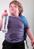 Ragazzo biondo sveglio con una bottiglia di acqua Fotografia Stock