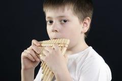 Ragazzo in camicia bianca che gioca panflute di bambù Fotografie Stock