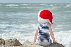 Ragazzo in cappello di Santa che si siede sulla spiaggia Vista posteriore Immagine Stock