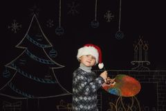 Ragazzo in cappello di Santa con una tavolozza dei colori su un fondo di Natale Fotografia Stock Libera da Diritti