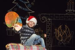 Ragazzo in cappello di Santa con una tavolozza dei colori su un fondo di Natale Fotografie Stock