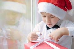 Ragazzo in cappello e farfallino di Santa che legano nastro su un regalo Fotografia Stock