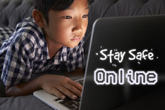 Ragazzo a casa facendo uso del computer portatile con il messaggio online sicuro di soggiorno Fotografia Stock