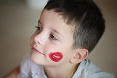 Ragazzo castana con un bacio rosso sulla sua guancia fotografie stock libere da diritti