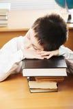 Ragazzo caucasico che dorme sui libri Fotografia Stock