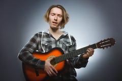 Ragazzo caucasico che gioca sulla chitarra acustica Adolescente con la chitarra di legno classica Fotografia Stock