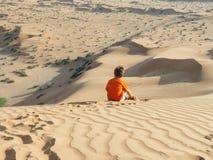 Ragazzo caucasico che si siede sulla retrovisione della duna di sabbia Fotografia Stock Libera da Diritti