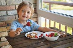 Ragazzo caucasico di 5 anni felice mangiare per le cialde viennesi della prima colazione con il gelato e le fragole immagine stock