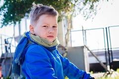 Ragazzo caucasico di sei anni dai capelli corti che esamina la macchina fotografica all'aperto fotografia stock