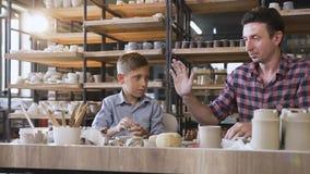 Ragazzo caucasico sveglio con suo padre che fa i vasi ceramici nelle terraglie video d archivio