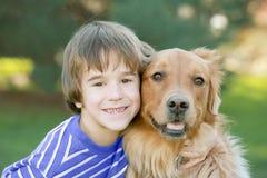 Ragazzo che abbraccia cane Fotografia Stock