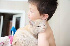Ragazzo che abbraccia con il gatto dopo avere svegliato, l'animale domestico favorito sulle mani del bambino, le interazioni fra  Immagine Stock Libera da Diritti