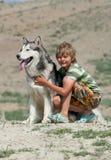 Ragazzo che abbraccia un cane lanuginoso Fotografie Stock Libere da Diritti