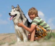 Ragazzo che abbraccia un cane lanuginoso Immagine Stock