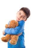 Ragazzo che abbraccia un orsacchiotto Fotografia Stock Libera da Diritti