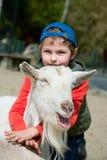Ragazzo che abbraccia una capra Immagine Stock