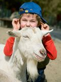 Ragazzo che abbraccia una capra Immagini Stock