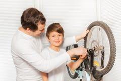 Ragazzo che aiuta suo padre che ripara i freni della bicicletta Fotografia Stock Libera da Diritti