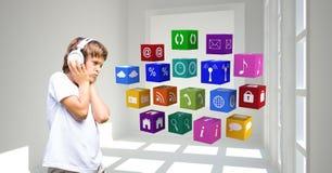 Ragazzo che ascolta la musica tramite le cuffie mentre esaminando le icone dei apps Fotografia Stock Libera da Diritti