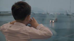 Ragazzo che aspetta il volo e che esamina gli aeroplani fuori video d archivio