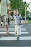 Ragazzo che attraversa la via ad un attraversamento Fotografia Stock Libera da Diritti