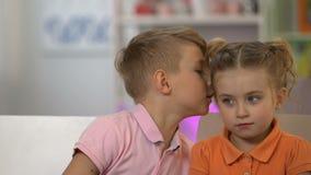 Ragazzo che bisbiglia alla ragazza, dicente le bugie alla piccola sorella innocente, pranking del fratello stock footage