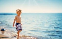Ragazzo che cammina in mare in cappello di paglia fotografia stock libera da diritti