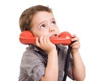 Ragazzo che comunica su un retro telefono. Fotografie Stock